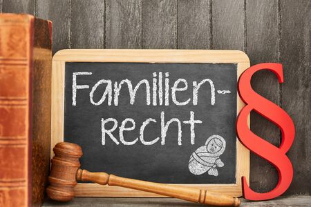 Specialist lawyer for German word Familienrecht (family law) as concept with law symbols next to blackboard 版權商用圖片