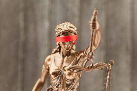 Justitia with blindfold as a justice concept in front of a wood background