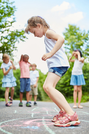 Girl jumps with concentration at hopscotch game in summer