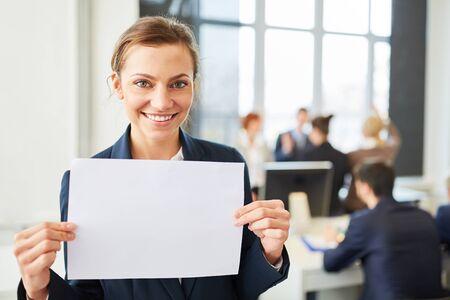Young businesswoman holds empty sign in office Stock Photo