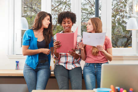 Three young women as students or apprentices are learning together in the office Standard-Bild