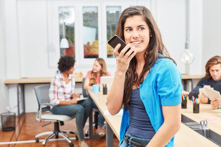 Young start-up woman is making a phone call with smartphone in open-plan office Standard-Bild