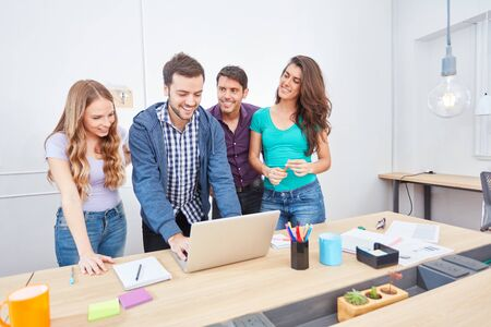 Young business start-up team together with programmer at laptop in office