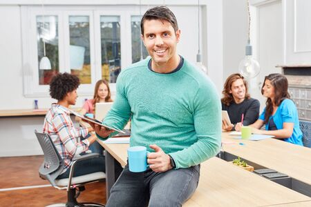 Young man as a successful entrepreneur in front of his team in the meeting Stock Photo