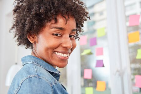 Young multicultural business woman in ideas workshop in front of a wall with sticky notes
