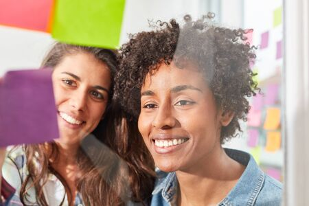 Two young women in a multicultural start-up team brainstorming together Standard-Bild