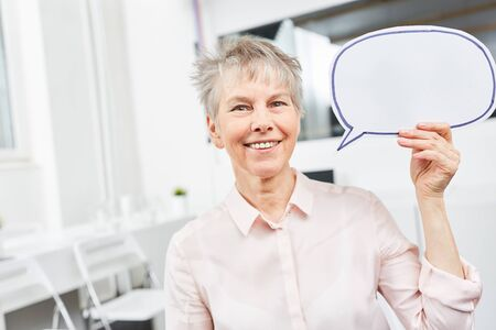 Senior business woman with speech bubble as communication concept Stock Photo