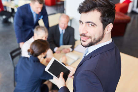 Man as founder manager in start-up business meeting with tablet