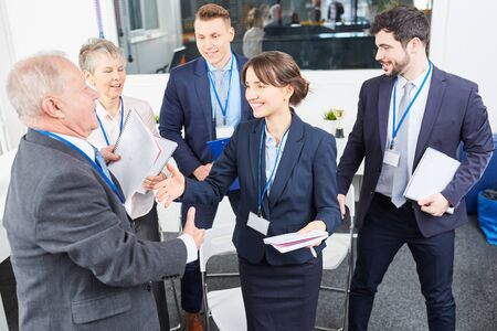 Business people congratulate business consultant speaker after successful seminar