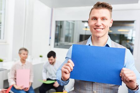 Joung start-up man holds blank page during creative brainstorming at office