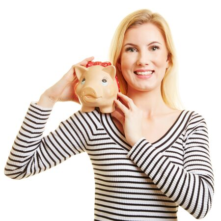 Young blond woman holds piggy bank in her hands Standard-Bild