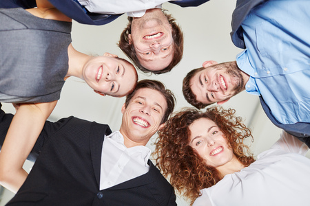 Business people putting heads together looking down Stock Photo