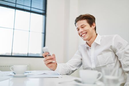 Smiling entrepreneur with smartphone reads SMS with joy Stock Photo