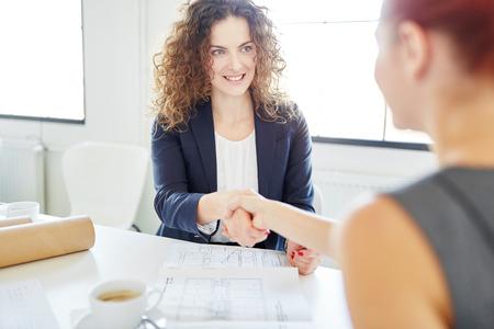 Handshake between businesswomen during application meeting