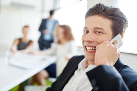 Successful entrepreneur on the phone in start-up meeting Stock Photo