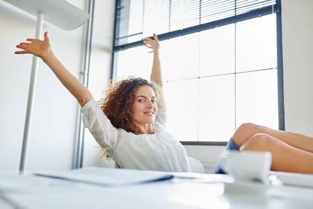 Happy businesswoman relaxing in her office