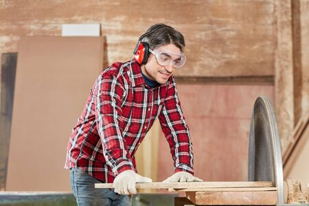 Man as carpenter with grinding machine and goggles