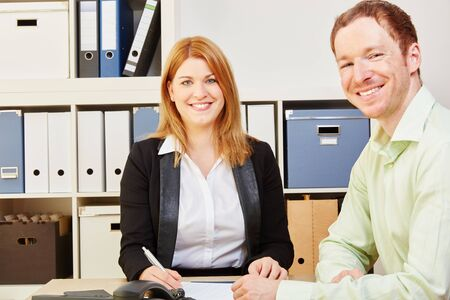 Two happy business people in their office smiling while working