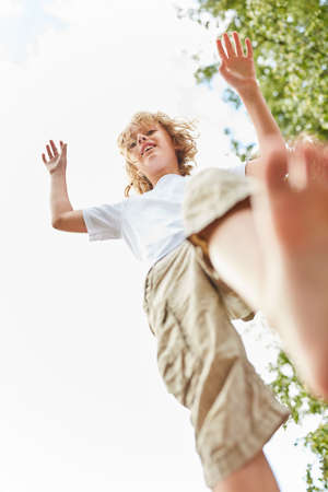 Boy plays and romps while keeping his balance outdoors