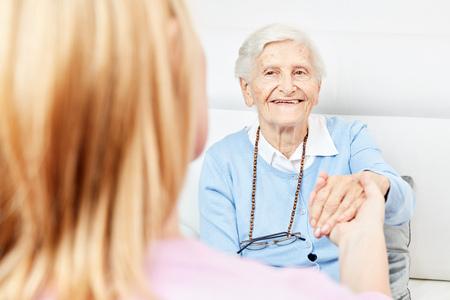 Nurse or nurse on home visit holding a seniors hand