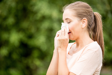 Woman with allergy or a cold sneezing with tissue
