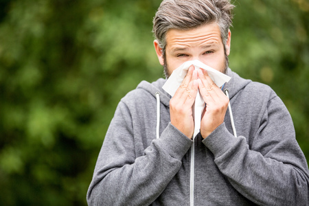 Man with allergy or ill with hay fever sneezing and cleaning nose