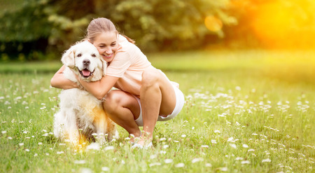Woman hugs and cuddles Golden Retriever dog and pets him with love