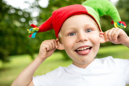 Boy wearing fool cap pulling his ears and having fun Imagens