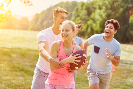 Group of teenagers playing rugby in the park in summer Stockfoto