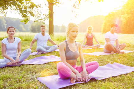 Yoga group doing relaxation exercise in summer at park Stock Photo