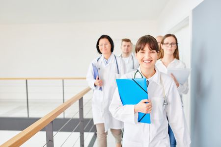 Young successful woman with team of doctors in hospital Stock Photo