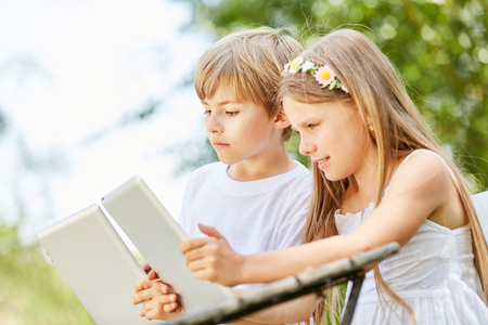 Boy and girl with tablet together make a computer course