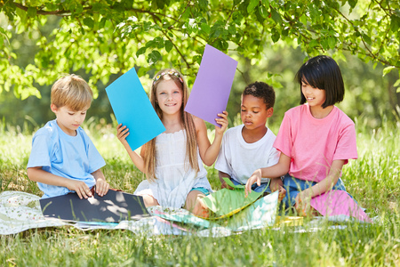 Multicultural group of children in creative tinkering in the summer in the park