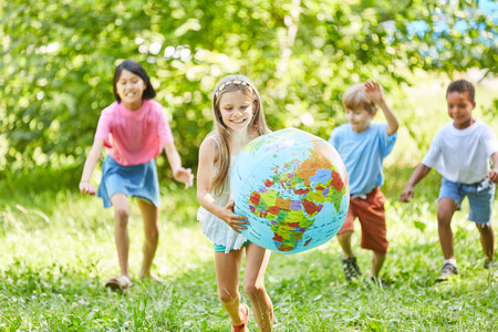 Happy girl carries globe and plays with friends in nature Stock Photo