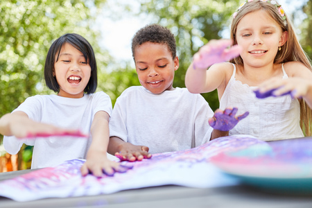Creative kids as friends play with finger paints on kids birthday