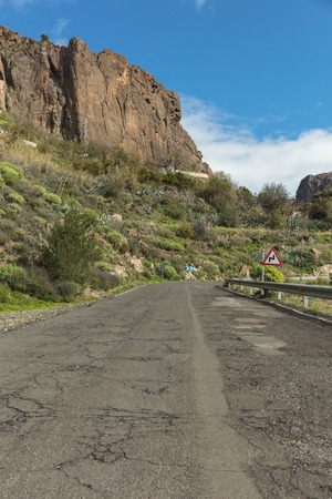 Roadway with broken asphalt and road sign in Gran Canaria 스톡 콘텐츠