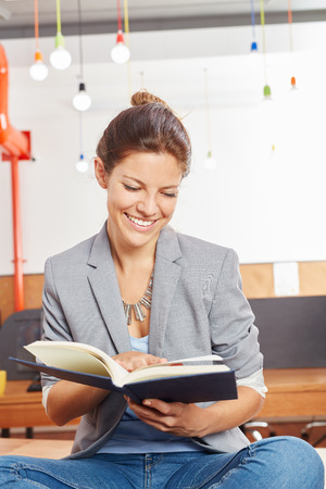 Woman reading training book for her studies Stock Photo