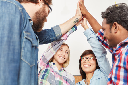 High Five with successful business team members as motivation Stock Photo