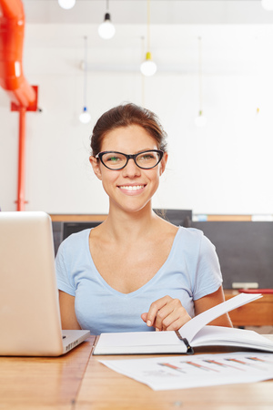 Young woman as student with laptop during her university studies Stock Photo