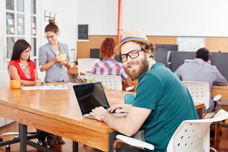 Nerd programmer with laptop in IT startup