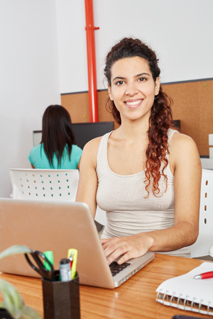 Woman writing with laptop in coworking office Stock Photo