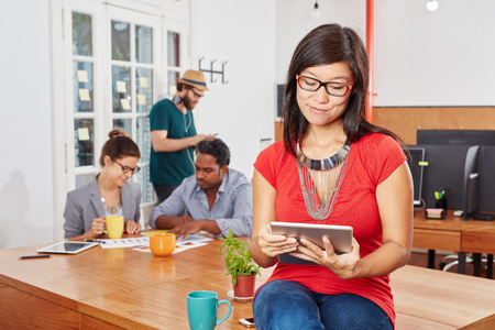 Young woman planning project with tablet in startup coworking office