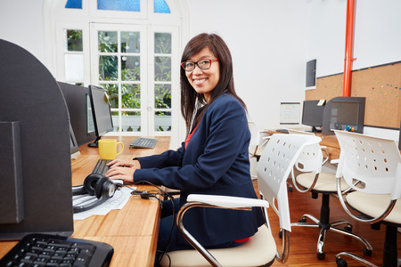 Asian woman as consultant in call center in her place of work