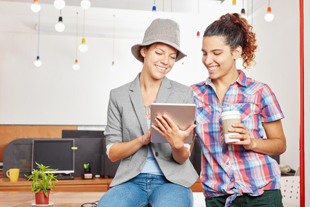 Women in start up as students using tablet for internet social media Stock Photo