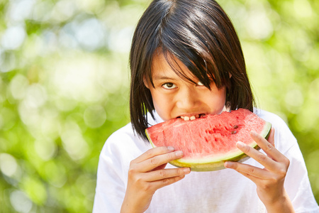 Asian girl is hungryly biting into a juicy watermelon