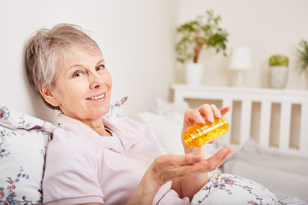 Senior woman as sick patient takes medication Stock Photo