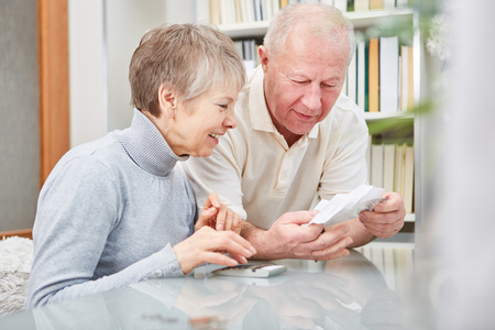 Senior couple holding receipts for doing finance accounting