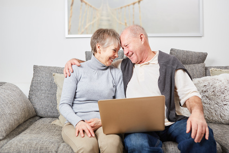 Happy seniors in love hug on the couch holding laptop Stock Photo