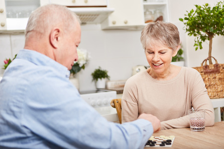 Seniors play board game for leisure and relaxation as couple in retirement activity