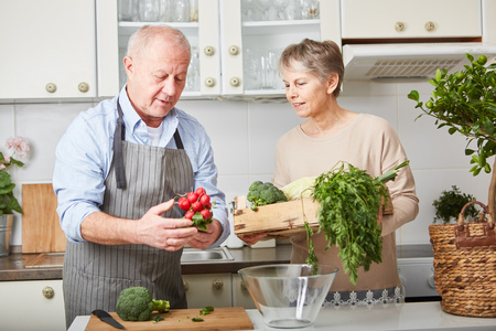 Senior couple cooking fresh and healthy vegetarian meal